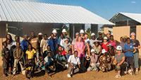 꿈을 이루다 : 국제 마라나타 자원봉사단에 참여한 현지인 및 외지인 봉사자들이 사진 촬영을 위해 새 건물 앞에서 포즈를 취하고 있다.