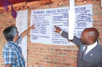 몰살당한 일가족: 뮤고네로 병원 외과 의사 제시 타바란자 박사와 서르완다합회장 조수에 루시네 목사가 대학살 중 사망한 가족들의 이름을 확인하고 있다.